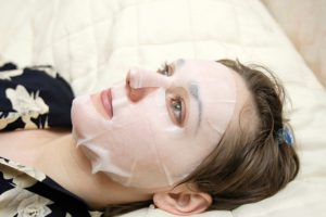 The woman lays  with a facial mask
